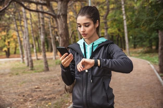 Foto van geweldige jonge mooie fitness vrouw buiten in het park kijken horloge klok met behulp van mobiele telefoon.