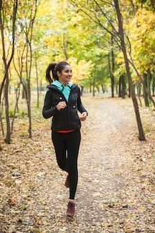 Foto van geweldige jonge mooie fitness vrouw loper buiten in het park loopt.