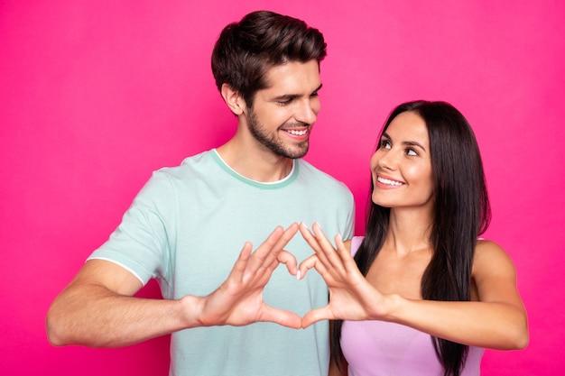 Foto van geweldige kerel en dame die hartfiguur maken met armen die gevoelens uiten op zoek ogen dragen casual outfit geïsoleerde roze kleur achtergrond