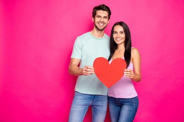 Foto van geweldige kerel en dame knuffelen met groot papieren hart in handen die positieve houding uitdrukken dragen casual outfit geïsoleerde roze kleur achtergrond
