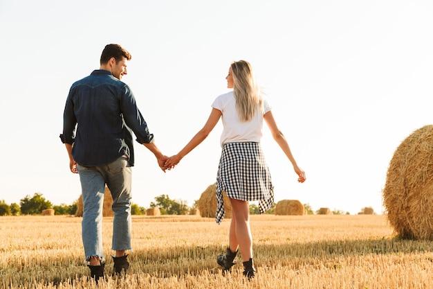 Foto van geweldige paar man en vrouw lopen door gouden veld met bos van hooibergen, tijdens zonnige dag