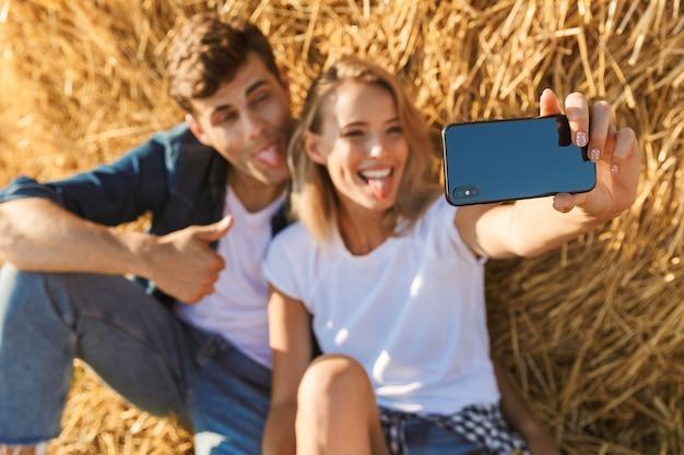 Foto van geweldige paar man en vrouw selfie te nemen zittend onder grote hooiberg in gouden veld, tijdens zonnige dag