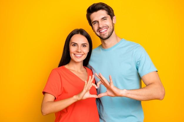 Foto van geweldige twee mensen man dame vieren valentijn dag houden vingers hart figuur vorm dragen casual blauw oranje t-shirts geïsoleerde gele kleur muur