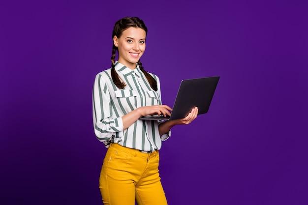 Foto van geweldige zakelijke dame freelancer bedrijf notebook handen schrijven werkende e-mail partners dragen gestreepte shirt gele broek geïsoleerde paarse kleur achtergrond
