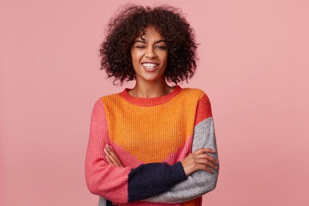 Foto van glamoureuze charismatische aantrekkelijke afro-amerikaanse meid met afro kapsel kijkt met vreugde, met een gelukkige glimlach, staan met gekruiste armen, knipoogt, heeft plezier, in kleurrijke longsleeve, geïsoleerd op roze