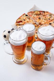 Foto van glazen met schuimbier, pizza op lege witte achtergrond