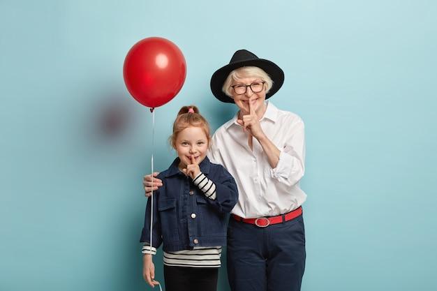 Foto van glimlachend klein schattig meisje en senior vrouw demonstreren stilte teken, geheim vertellen, hebben blije uitdrukking, voel me opgewonden, kom op feestelijke gebeurtenis, geïsoleerd over blauwe muur. zwijg, wees stil