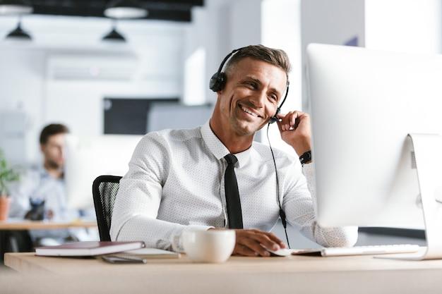Foto van glimlachende exploitantman 30s die bureaukleren en hoofdtelefoon dragen, die door computer in call centre zitten
