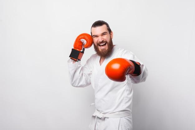 Foto van glimlachende man in taekwondo uniforme training over witte muur