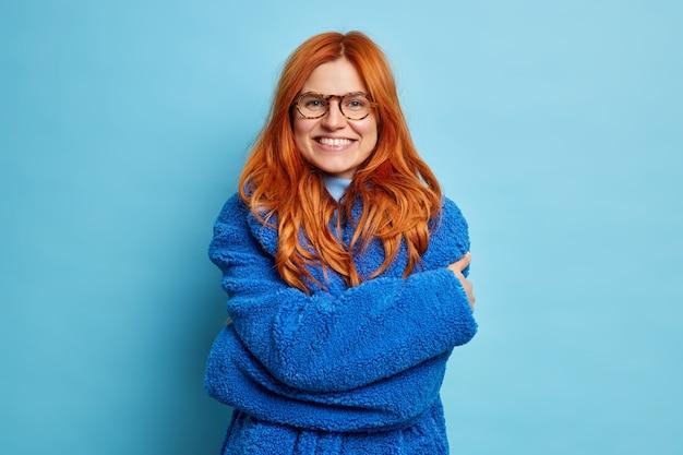 Foto van glimlachende roodharige europese vrouw knuffelt zichzelf en toont witte tanden gekleed in zachte vachtdoek voelt warmte in goed humeur.