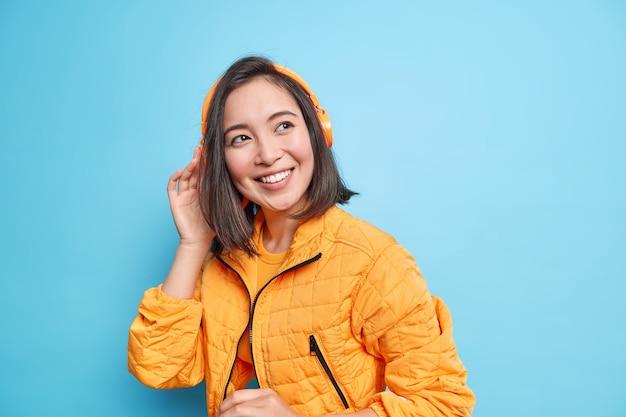 Foto van goed uitziende tienermeisje met oosterse uitstraling luistert muziek in moderne koptelefoon glimlacht breed draagt oranje modieuze jas geïsoleerd over blauwe muur. geweldige afspeellijst. muziek liefhebber