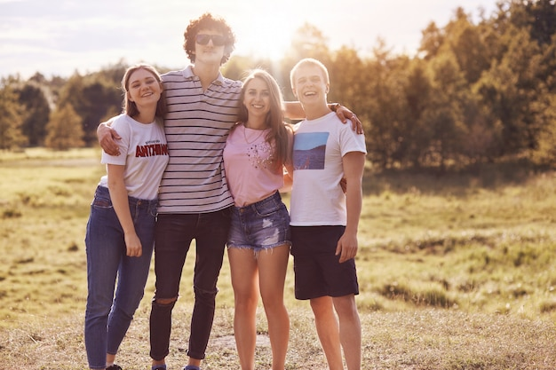 Foto van goede vrienden staan buiten, picknicken samen, omhelzen en glimlachen, hebben een goede relatie, gekleed in casual zomerkleding. mensen, gezelschap, rust concept