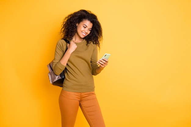 Foto van golvende vrolijke positieve vrij zoete mooie zwarte jongere dragen broek broek oranje in de buurt van lege ruimte staren naar telefoon geïsoleerd met handtas over gele levendige kleuren achtergrond