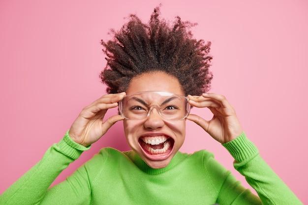 Foto van grappig gek krullend meisje heeft mond geopend toont tanden houdt handen op transparante bril draagt groene coltrui die erg emotioneel is maakt grimas,