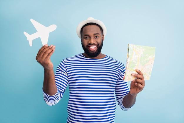 Foto van grappige aantrekkelijke donkere huid man reiziger houdt papieren vliegtuig kaart klaar om naar het buitenland te reizen dragen witte zonnepet gestreept zeeman shirt geïsoleerde blauwe kleur muur