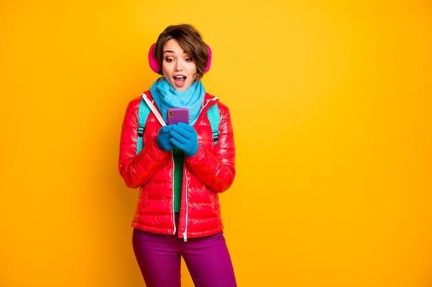 Foto van grappige blogger dame kijk telefoonscherm lees positieve reacties houdt van dragen casual rode jas blauwe sjaal handschoenen oorbedekking broek