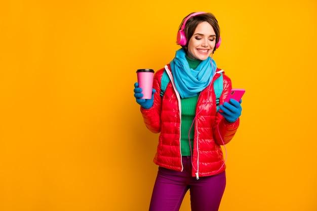 Foto van grappige blogger dame lopen straat houden telefoon luisteren oortelefoons jeugdmuziek drinken hete koffie dragen casual rode jas blauwe sjaal handschoenen broek