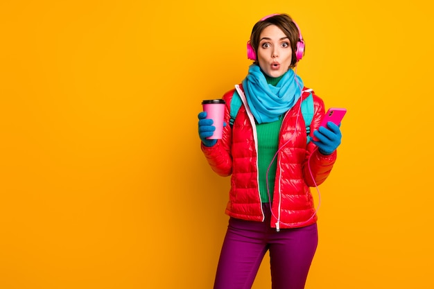 Foto van grappige blogger dame open mond houden telefoon luisteren oortelefoons jeugdmuziek koffie drinken dragen casual rode jas blauwe sjaal handschoenen broek