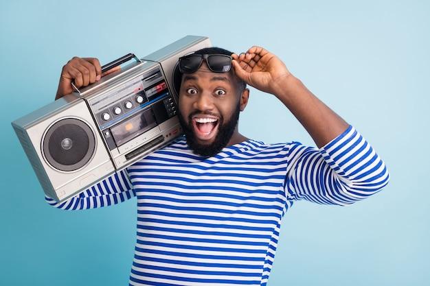Foto van grappige coole kerel met open mond houdt retro cassetterecorder