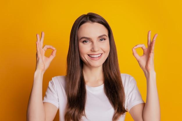 Foto van grappige dame toont twee ok-tekens en draagt een wit t-shirt dat op een gele achtergrond staat