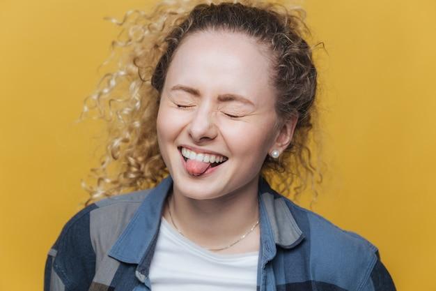 Foto van grappige dolblij vrouw heeft alleen plezier, lacht vrolijk en toont tong, houdt ogen dicht