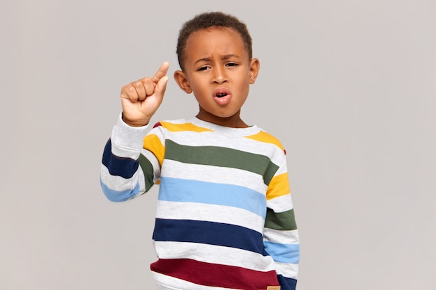 Foto van grappige donkere schooljongen in stijlvolle gestreepte trui met teleurgestelde gezichtsuitdrukking, gebaar met vingers maken alsof hij iets heel kleins vasthoudt. korting, verkoop en kleine prijs