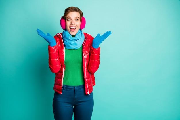 Foto van grappige gekke dame hand in hand opgeheven opgewonden gevoelens kerst verrassing dragen casual rode overjas blauwe sjaal roze oorbeschermers trui broek geïsoleerd groenblauw kleur muur