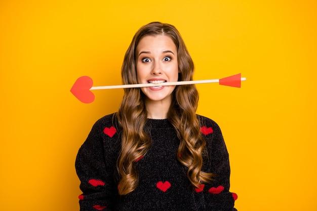 Foto van grappige gekke dame werkt als cupido pijl in de mond klaar om mensen te geven paren liefde gevoelens dragen harten patroon trui