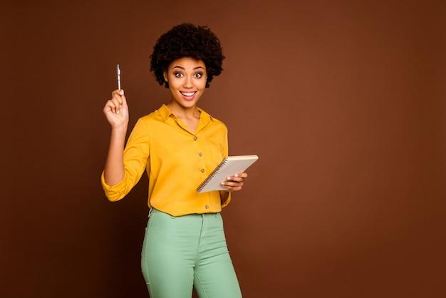 Foto van grappige gekke donkere huid golvende dame auteur houden dagboek verhogen pen hebben creatieve gedachte inspiratie moment dragen geel shirt groene broek geïsoleerde bruine kleur