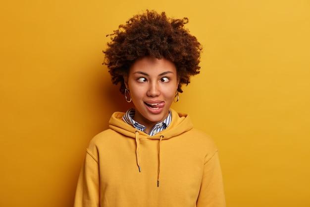 Foto van grappige jonge vrouw heeft een gek gezicht, kruist vingers en steekt tong uit, dwazen rond, draagt casual sweatshirt, poseert tegen gele muur. komische gezichtsuitdrukkingen concept