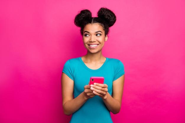 Foto van grappige jongere donkere huid dame houdt telefoon handen kijken zijkant lege ruimte