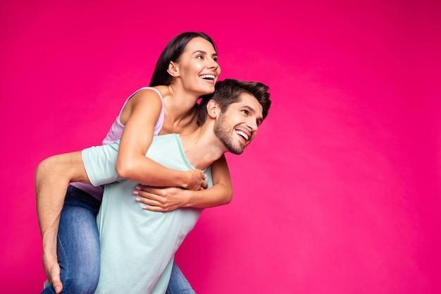 Foto van grappige kerel en dame die piggyback houden die vrije tijd doorbrengen op zoek ver weg dragen vrijetijdskleding geïsoleerde levendige levendige roze kleur achtergrond