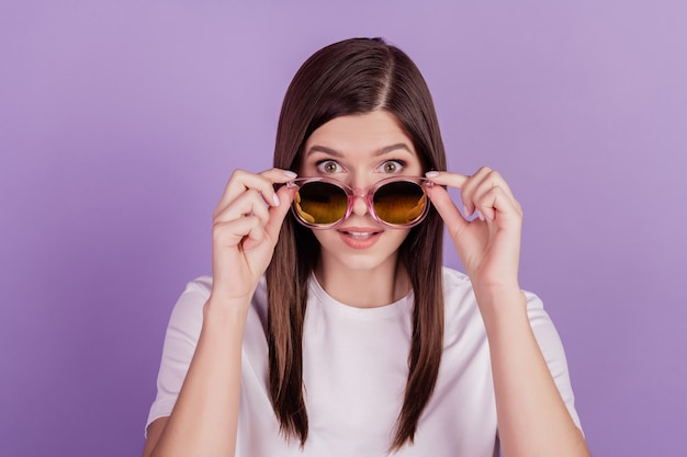 Foto van grappige meisjesaanrakingszonnebril die op violette achtergrond wordt geïsoleerd
