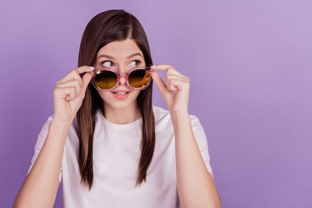 Foto van grappige meisjesaanrakingszonnebril ziet er lege ruimte uit geïsoleerd op violette achtergrond