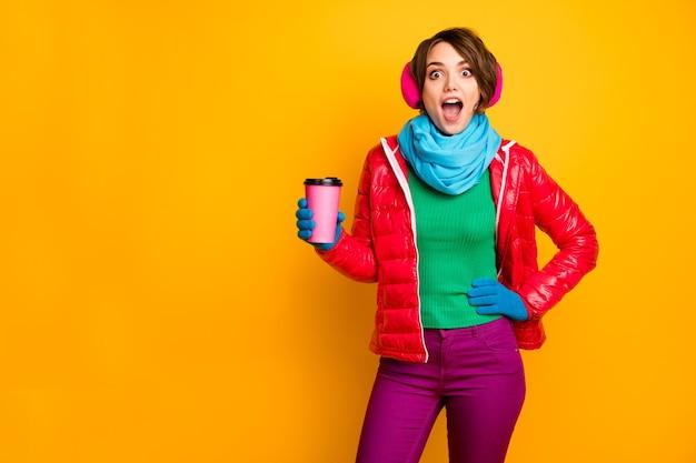Foto van grappige mooie dame houd papieren mok hete afhalen koffie luister goed nieuws open mond dragen casual rode jas blauwe sjaal handschoenen oor covers broek