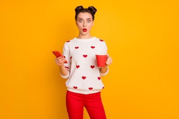 Foto van grappige mooie dame houdt warme koffie drank browsen telefoon open mond lezen shock nieuws slijtage harten patroon witte trui