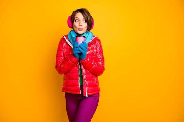 Foto van grappige mooie dame met papieren beker warme meeneem koffie opwarming koude dag dragen casual rode jas blauwe sjaal handschoenen oor covers broek