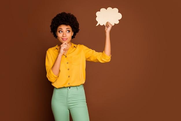 Foto van grappige mooie donkere huid krullende dame houdt lege papieren wolk na te denken over creatieve dialoog antwoord dragen geel shirt groene broek geïsoleerde bruine kleur