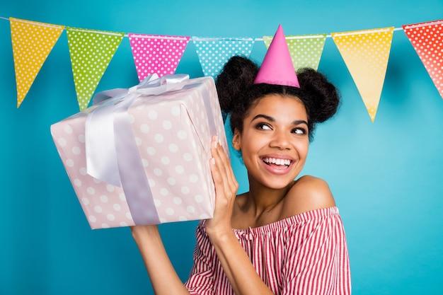 Foto van grappige nieuwsgierige donkere huid dame houdt grote geschenkdoos verjaardagsmeisje feestkleding kegelmuts rood wit gestreept shirt naakte schouders kleurrijke gestippelde vlaggen hangen over blauwe muur