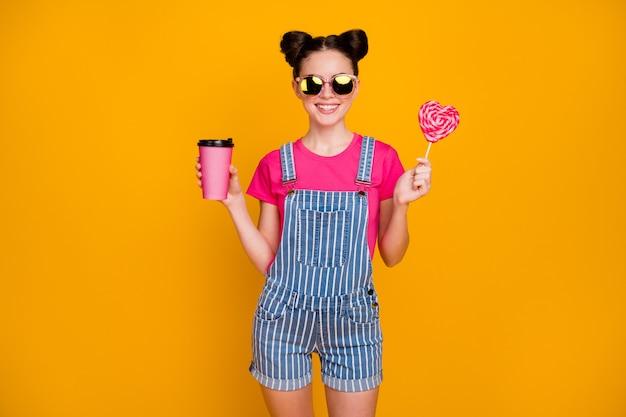 Foto van grappige tienerdame houdt hartvorm lolly snoep hete afhaalkoffie