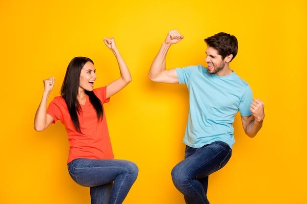 Foto van grappige twee mensen man dame vieren favoriete voetbal team winnen vuisten verheugend dragen casual blauw oranje t-shirts spijkerbroek geïsoleerde gele kleur muur