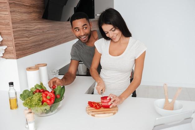Foto van grappige verliefde paar in de keuken koken. de mens neemt de producten weg.