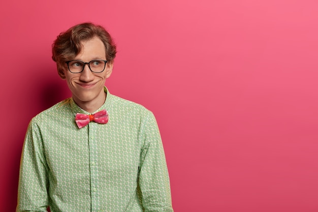Foto van grappige vrolijke man draagt elegant groen shirt en vlinderdas, transparante bril, heeft vrolijke positieve blik opzij, plant iets in gedachten, geïsoleerd op roze muur, kopie ruimte voor tekst