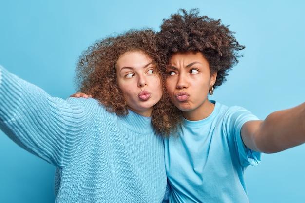 Foto van grappige vrouwen van gemengd ras die lippen pruilen en grimassen omarmen strekarmen om selfie te maken draag blauwe vrijetijdskleding in één toon met muurspel en breng samen vrije tijd door
