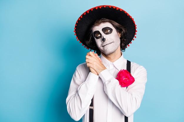 Foto van grappige zombie schepsel man dood dag griezelige make-up maskerade dromerig opzoeken armen samen denk dode bruid catrina calavera draag latino hoed kostuum geïsoleerde blauwe kleur achtergrond