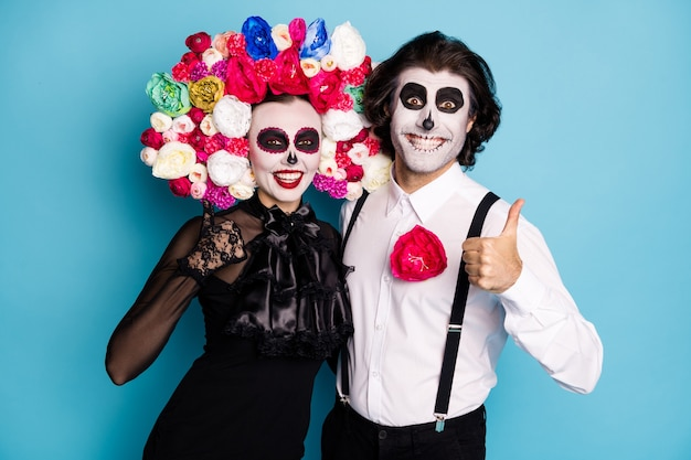 Foto van griezelig beangstigend twee mensen man dame knuffelen duim omhoog houden van festival service dragen zwarte jurk dood kostuum rozen hoofdband bretels geïsoleerde blauwe kleur achtergrond Premium Foto