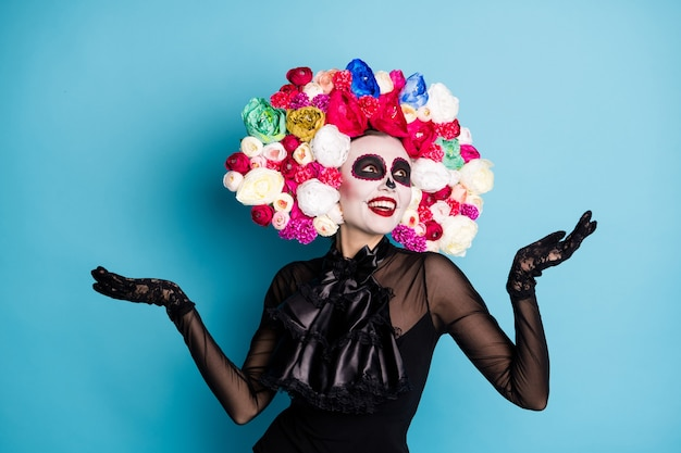 Foto van griezelig monster ondode schepsel dame kijk omhoog hemel vang sneeuwvlokken onverwacht herfstweer draag zwarte kanten jurk dood kostuum rozen hoofdband geïsoleerde blauwe kleur achtergrond