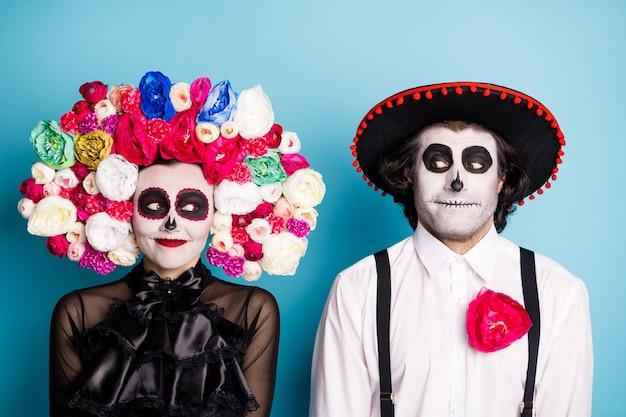Foto van griezelig monster paar man dame speelse look zombie eerste ontmoeten na opstanding dragen zwarte jurk dood kostuum rozen hoofdband bretels sombrero geïsoleerde blauwe kleur achtergrond
