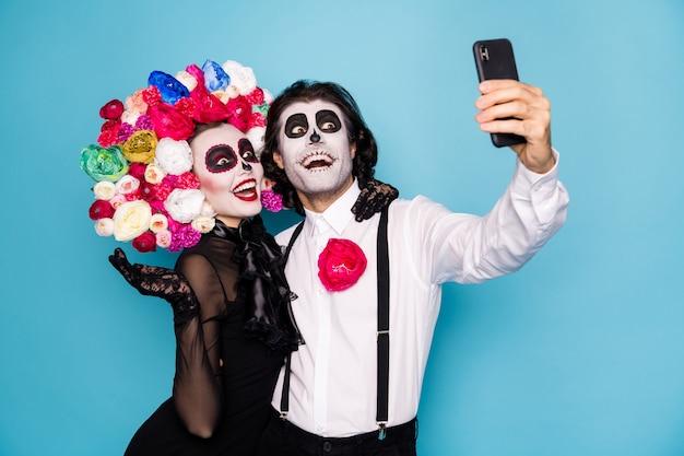 Foto van griezelig paar man dame knuffel vasthouden telefoon maken selfie video-oproep vriend dragen zwarte jurk dood kostuum masker suiker schedel rozen hoofdband bretels geïsoleerde blauwe kleur achtergrond