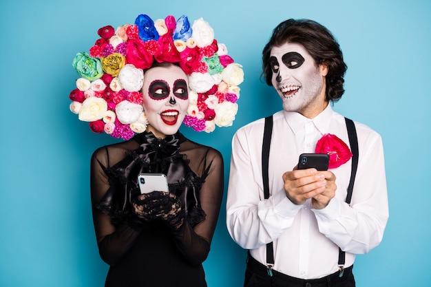 Foto van griezelig stel man dame houd telefoons lees donkere humor grappen deel grappige berichten draag zwarte jurk dood kostuum suikerschedel rozen hoofdband bretels geïsoleerde blauwe kleur achtergrond